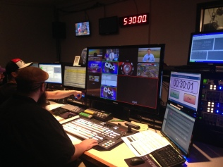 Workers direct the evening newscast from the station's control room.